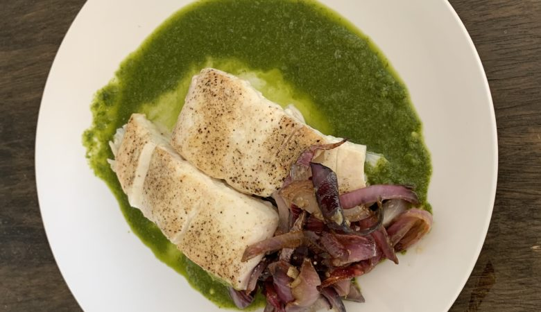 Halibut with Cilantro Lime Sauce and Red Onions on a White Plate