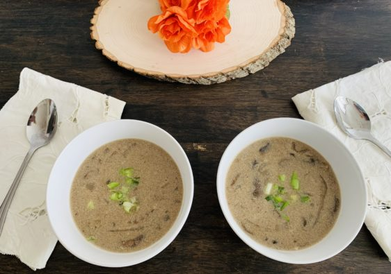 Cream of Mushroom Soup on Table with Napkins, Spoons, Wood and Orange Flowers